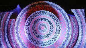 """Urban Art Kunst Patrick Hartl werk Adam Stubley Lasst Blumen sprechen! Die Kommunikation des Menschen mit Blumen reicht weit zurück, die alten Ägypter nutzten sie, im Osmanischen Reich wurde eine echte Wissenschaft daraus, und heute kennt man das Sprichwort """"Blumen sind das Lächeln der Erde"""". Tollwood-Künstler Adam Stubley hat für diesen Winter eine acht Meter hohe Fantasieblume gebaut. Rot leuchtend empfängt sie die Besucher im Eingangsbereich und soll ihnen ein Lächeln ins Gesicht zaubern."""